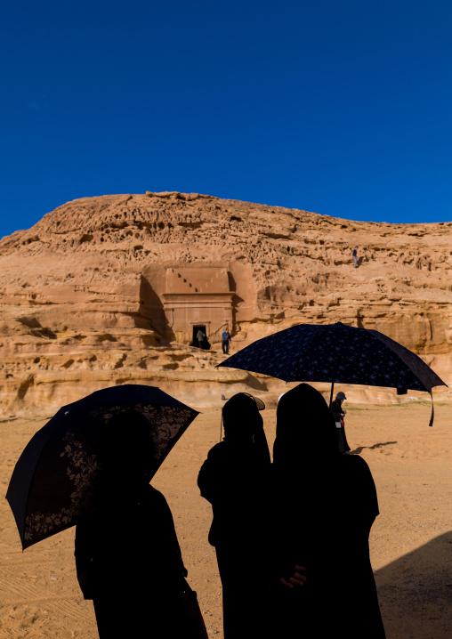Tourists in front of a nabataean tomb in madain saleh archaeologic site, Al Madinah Province, Al-Ula, Saudi Arabia