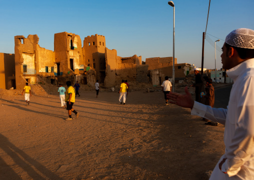 Saudi men playing football in the middle of old houses, Najran Province, Najran, Saudi Arabia