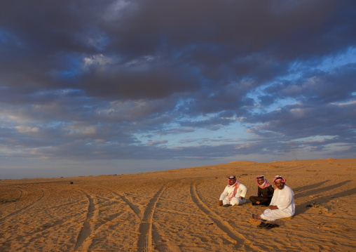 Saudi men resting in the desert, Al-Jawf Province, Al-Nefud, Saudi Arabia