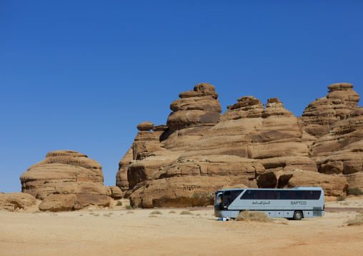 Tourists bus in front of a Nabataean tomb in al-Hijr archaeological site in Madain Saleh, Al Madinah Province, Alula, Saudi Arabia