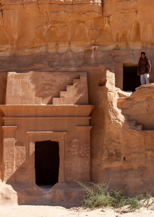 Saudi tourist climbing on a nabataean tomb in madain saleh archaeologic site, Al Madinah Province, Al-Ula, Saudi Arabia