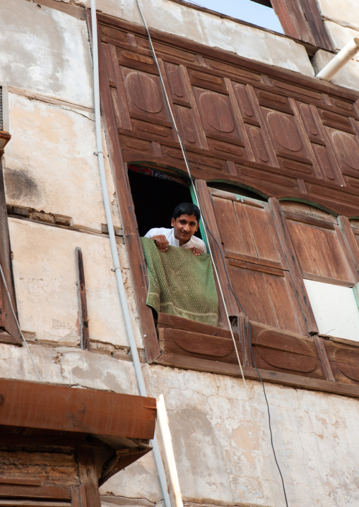 Man looking out from a house with wooden mashrabia and rowshan in the old quarter, Hijaz Tihamah region, Jeddah, Saudi Arabia