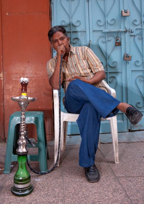 Man smoking water pipe in the street, Hijaz Tihamah region, Jeddah, Saudi Arabia