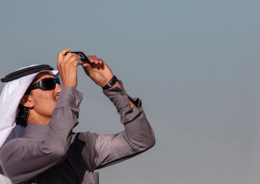 Saudi tourist taking pictures with his mobile phone, Riyadh Province, Riyadh, Saudi Arabia