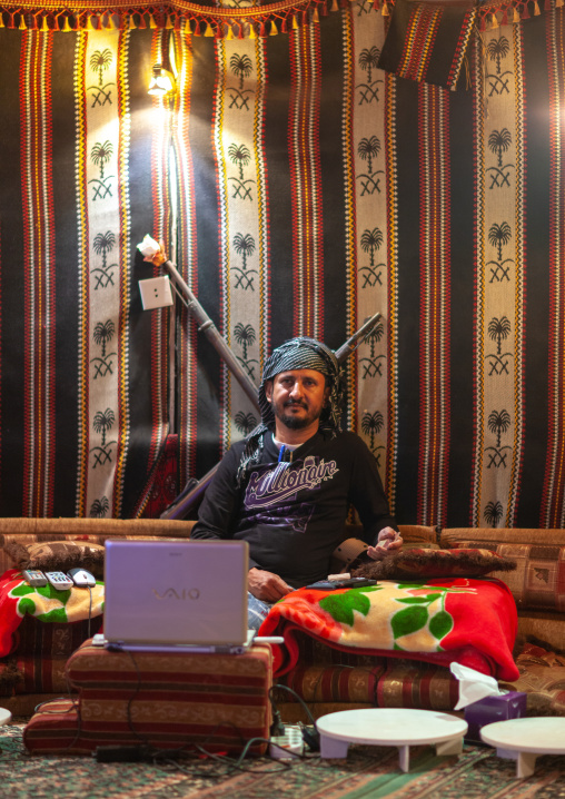 Saudi man using his computer inside his tent, Al-Sarawat, Fifa Mountains, Saudi Arabia