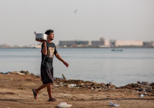 Asian foreign worker carrying fish, Jizan Region, Jizan, Saudi Arabia