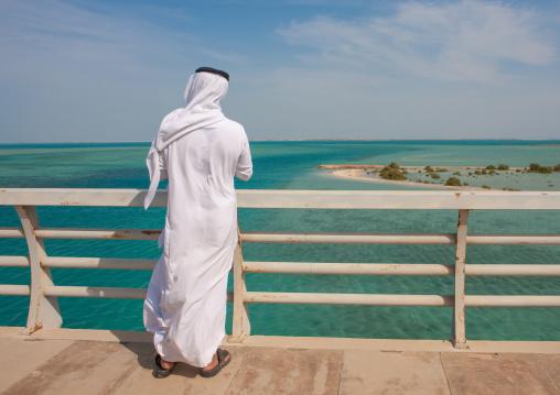 Rear view of a saudi man looking at the red sea from a bridge, Jizan Region, Farasan island, Saudi Arabia