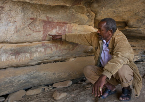 Laas Geel Rock Art Caves, A Squatting Guide Explaining The Meaning Of Paintings, Somaliland