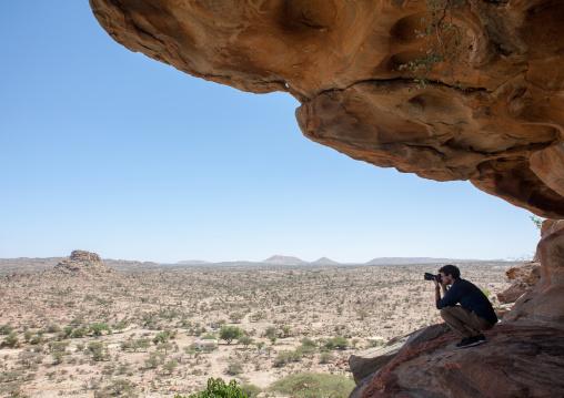 Western tourist taking pictures in laas geel rock art caves, Woqooyi Galbeed region, Hargeisa, Somaliland