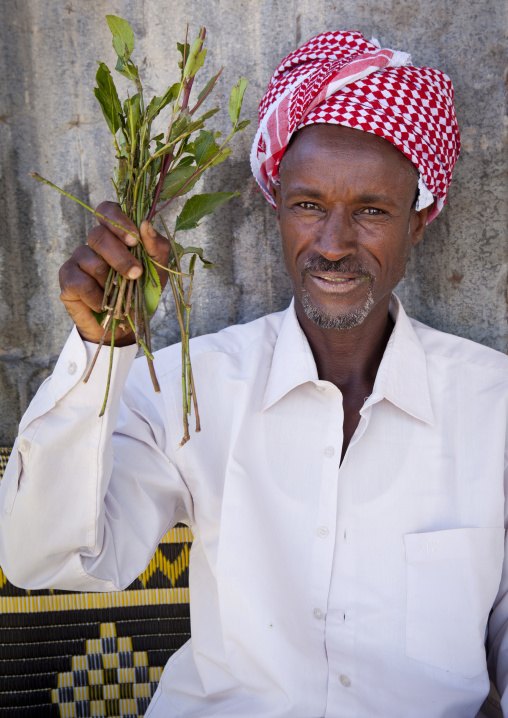 A Man Wearing A White Shirt Holding A Branch Of Khat In His Hand Sitting In A Street Of Burao, Somaliland