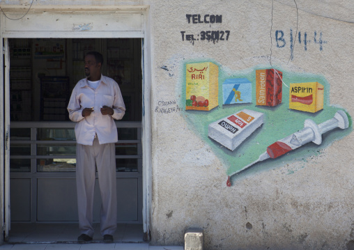 A Man Standing Inside A Medical Dispensary With Painted Advertisment Onto The Wall, Boorama, Somaliland