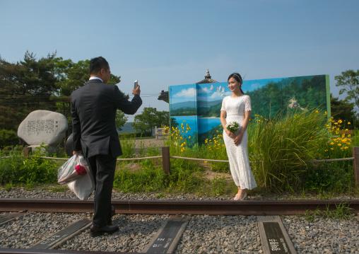 North korean defector joseph park taking a picture of his south korean fiancee juyeon on the north and south korea border, Sudogwon, Paju, South korea