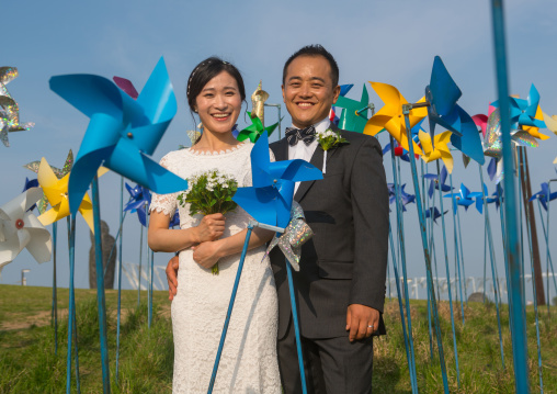 North korean defector joseph park with his south korean fiancee called juyeon in the middle of windmills in imjingak park, Sudogwon, Paju, South korea