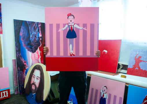 Sun mu artist hiding behind a painting of his happy children serie, National capital area, Seoul, South korea