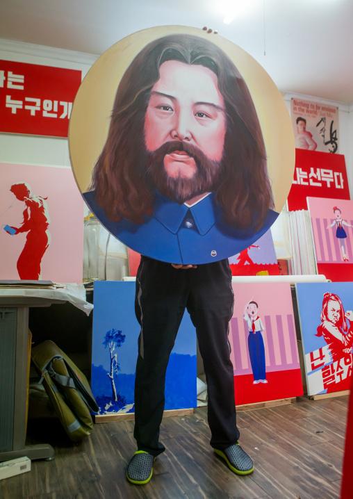 Sun mu artist hiding behind a painting of kim jong il looking like jesus, National capital area, Seoul, South korea