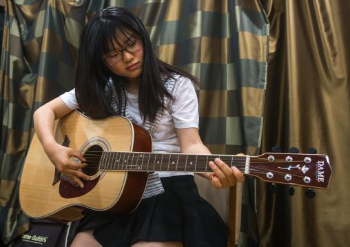 North korean teen defector in yeo-mung alternative school playing guitar, National capital area, Seoul, South korea