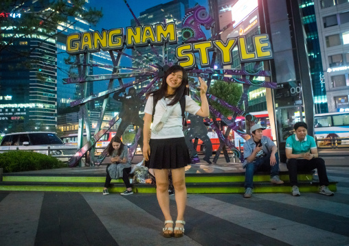 North korean teen defector in front of a gangnam style logo, National capital area, Seoul, South korea