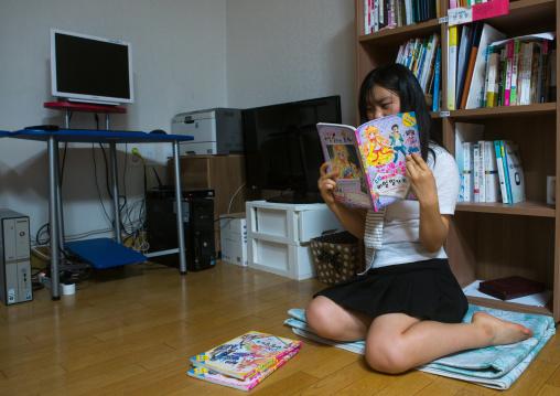 North korean teen defector reading a korean manga book, National capital area, Seoul, South korea