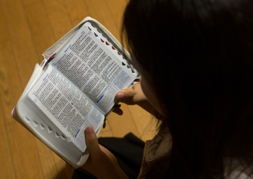 North korean teen defector reading the bible, National capital area, Seoul, South korea