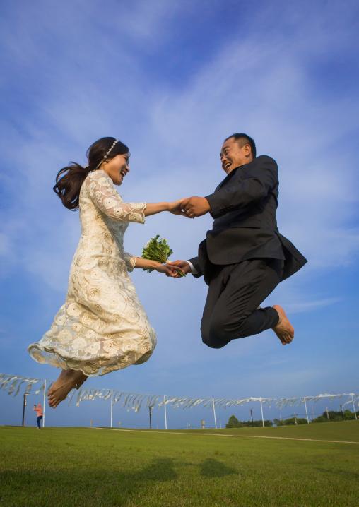 North korean defector joseph park with his south korean fiancee called juyeon jumping in imjingak park, Sudogwon, Paju, South korea