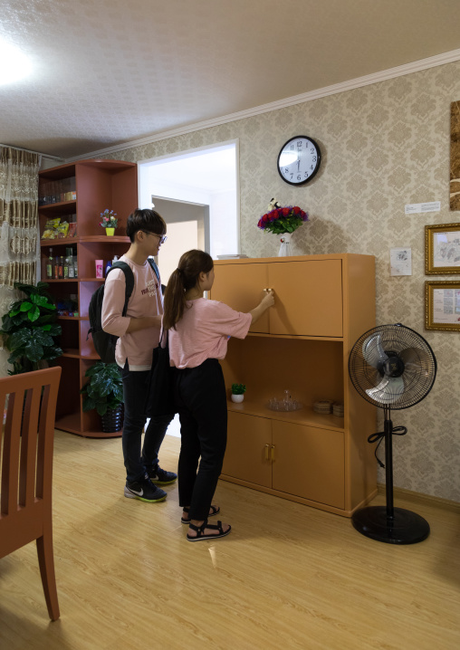 South Korean visitors looking in a cupboard during the exhibition Pyongyang sallim at architecture biennale showing a north Korean apartment replica, National Capital Area, Seoul, South Korea