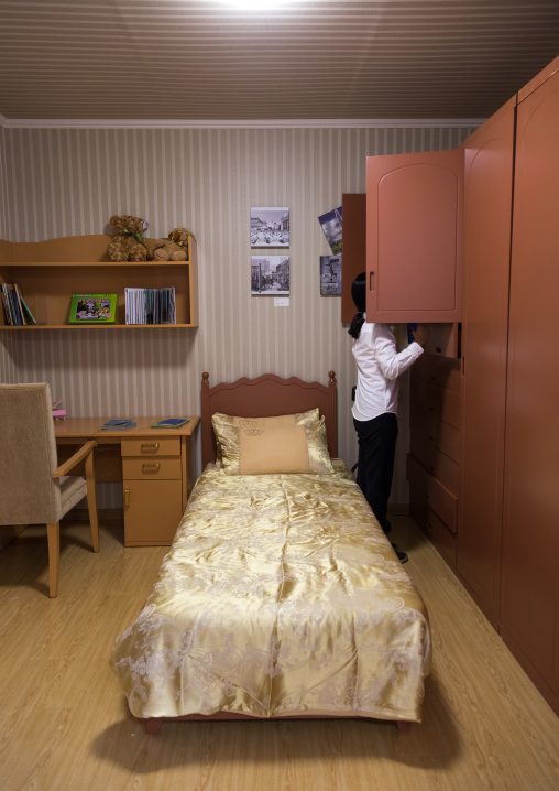 South Korean visitor looking in a cupboard of a bedroom during the exhibition Pyongyang sallim at architecture biennale showing a north Korean apartment replica, National Capital Area, Seoul,