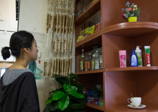 South Korean visitor looking at bottles during the exhibition Pyongyang sallim at architecture biennale showing a north Korean apartment replica, National Capital Area, Seoul, South Korea