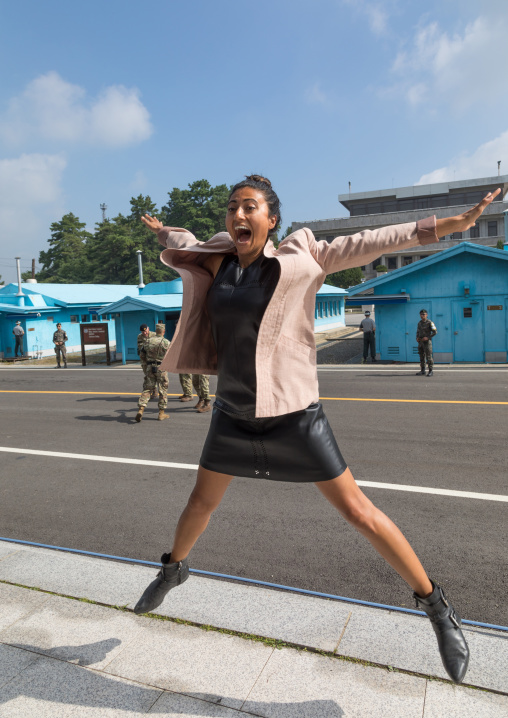 Tourist jumping for a photo souvenir in the joint security area on the border between the two Korea, North Hwanghae Province, Panmunjom, South Korea