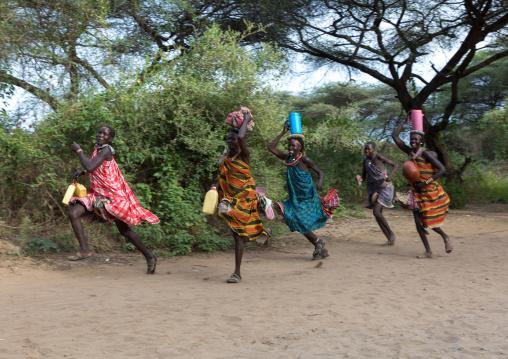 Toposa tribe women running with stuff on their heads, Namorunyang State, Kapoeta, South Sudan