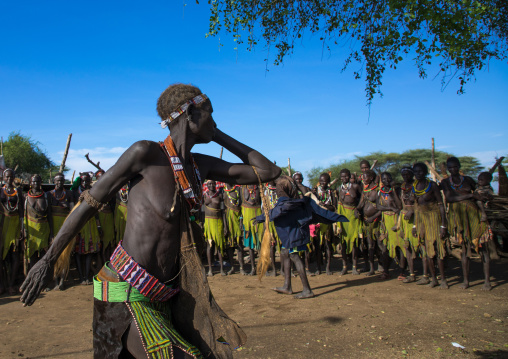 Toposa tribe woman in traditional clothing dancing during a ceremony, Namorunyang State, Kapoeta, South Sudan