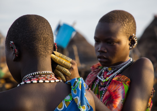 Toposa tribe woman with huge rings putting earrings to a friend, Namorunyang State, Kapoeta, South Sudan