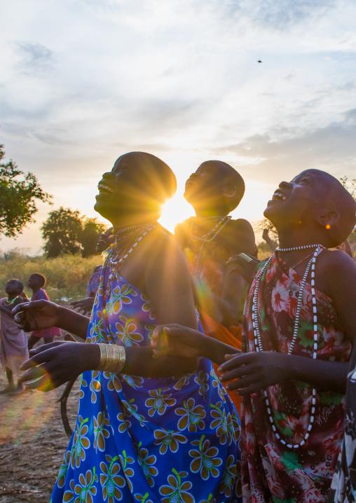 Toposa tribe women in traditional clothing looking at the sky, Namorunyang State, Kapoeta, South Sudan
