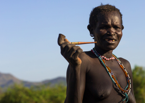 Larim senior tribe woman smoking pipe, Boya Mountains, Imatong, South Sudan