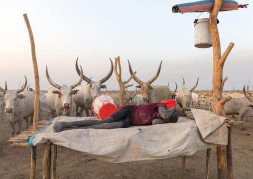 Mundari tribe boy resting on a bed in a cattle camp, Central Equatoria, Terekeka, South Sudan