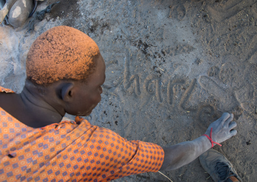 Mundari tribe man with hair dyed in orange with cow urine writing his name in the ashes, Central Equatoria, Terekeka, South Sudan