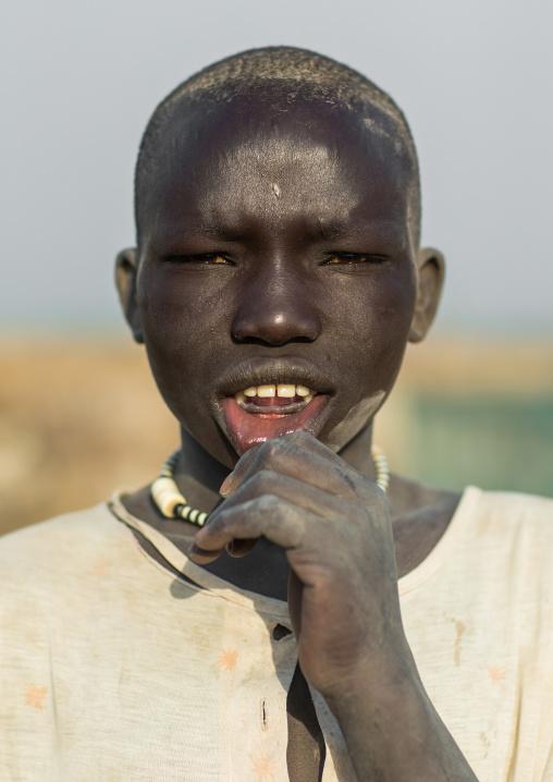 Portrait of a Mundari tribe boy shiwing his lower teeth traditionally removed, Central Equatoria, Terekeka, South Sudan
