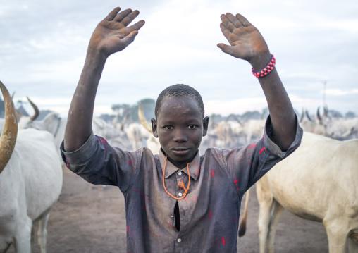 A Mundari tribe boy mimics the position of horns of his favourite cow, Central Equatoria, Terekeka, South Sudan