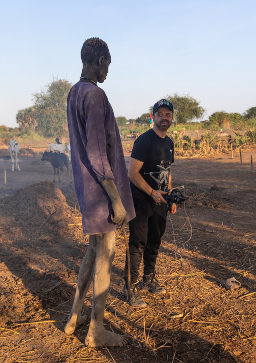 Western tourist with a tall Mundari man, Central Equatoria, Terekeka, South Sudan