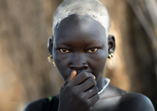 Portrait of a beautiful Mundari young woman with ash on the head to dye her hair in red, Central Equatoria, Terekeka, South Sudan