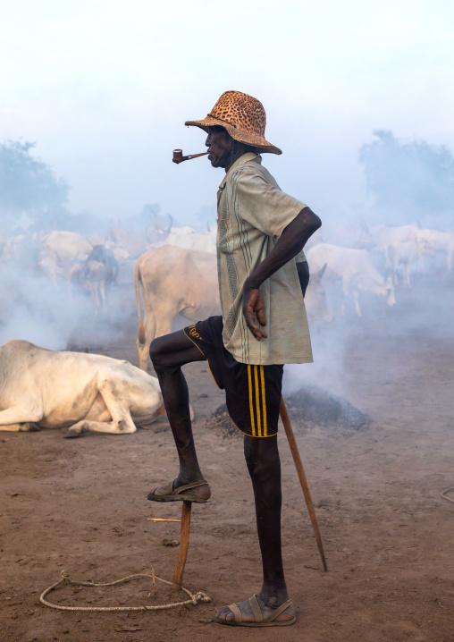 Portrait of a Mundari tribe man smoking a pipe while monitoring his cows, Central Equatoria, Terekeka, South Sudan