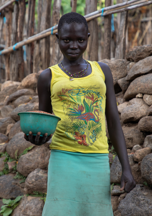 Lotuko tribe woman carrying food in front of a stone wall, Central Equatoria, Illeu, South Sudan