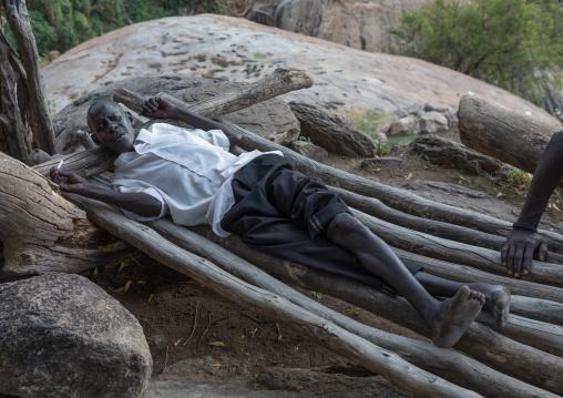 Lotuko tribe man resting on a wood bed, Central Equatoria, Illeu, South Sudan