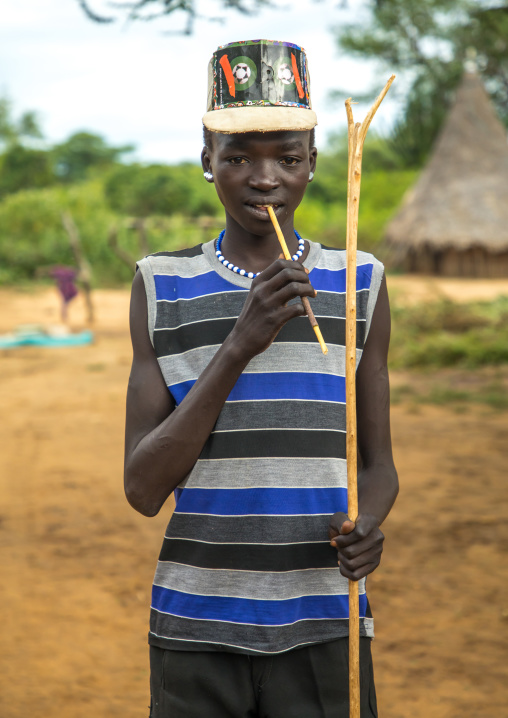 Larim tribe boy with a fashionnable look using a wooden toothbrush, Boya Mountains, Imatong, South Sudan