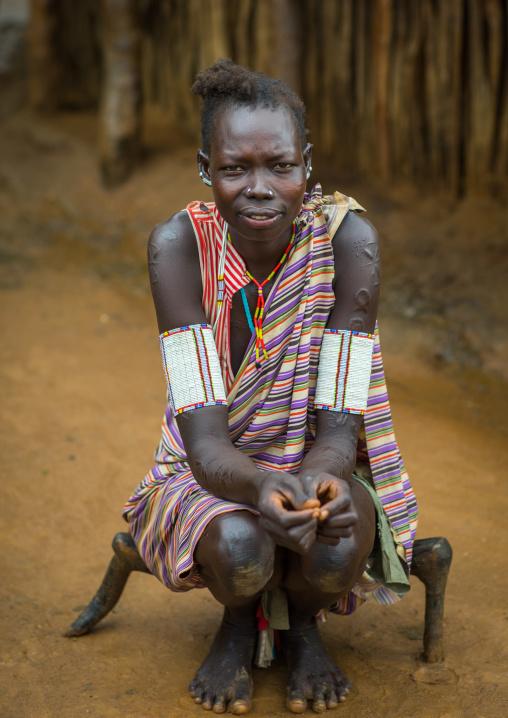 Portrait of a Larim tribe woman sit on a wooden seat, Boya Mountains, Imatong, South Sudan
