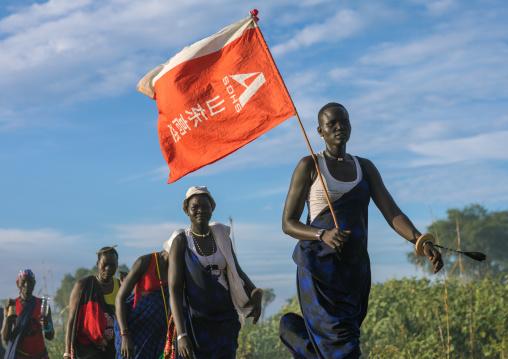 Mundari tribe women with a chinese flag celebrating a wedding, Central Equatoria, Terekeka, South Sudan