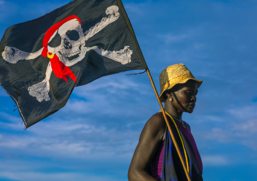 Mundari tribe woman with a pirate flag while celebrating a wedding, Central Equatoria, Terekeka, South Sudan