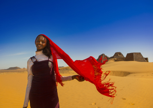 Sudan, Kush, Meroe, young sudanese woman in front of the pyramids and tombs in royal cemetery