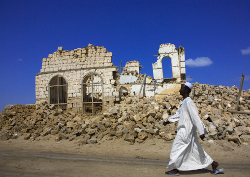 Sudan, Port Sudan, Suakin, man passing in front of a ruined ottoman coral buildings