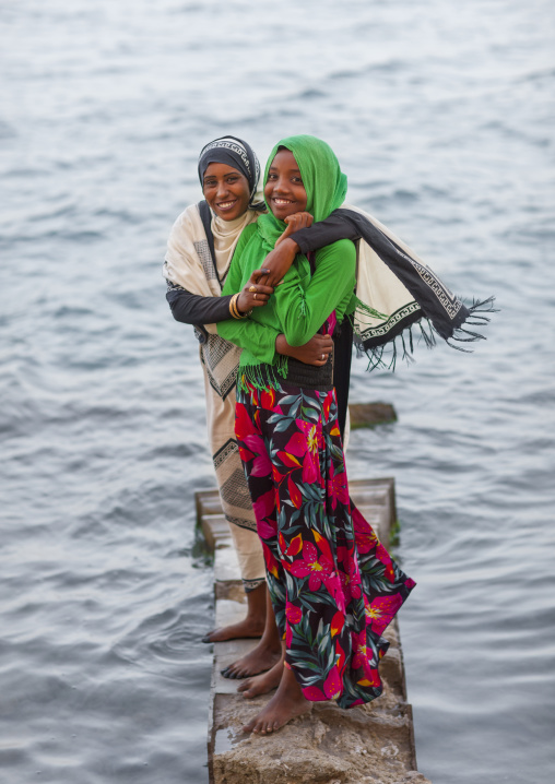 Sudan, Port Sudan, Suakin, girls standing on a rock on the red sea bank