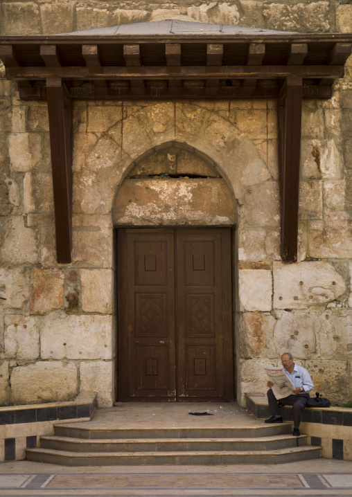 Man Reading Near An Old Door, Damascus, Damascus Governorate, Syria